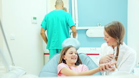 Lächelnder Zahnarzt, der dem jungen Patienten, Assistent Instrumente im Hintergrund zeigt stock footage