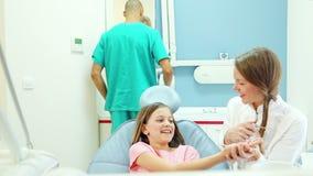 Lächelnder Zahnarzt, der dem jungen Patienten, Assistent Instrumente im Hintergrund zeigt stock video footage