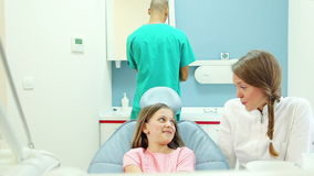 Lächelnder Zahnarzt, der mit jungem weiblichem Patienten, männlicher Chirurg im Hintergrund spricht stock video