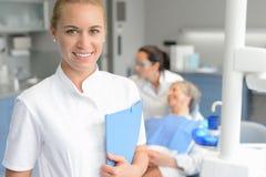 Lächelnder Zahnarzt des Zahnarzthelfers mit Patienten lizenzfreie stockbilder