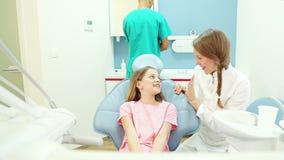 Lächelnder Zahnarzt spricht mit jungem weiblichem Patienten, männlicher Chirurg im Hintergrund stock video footage