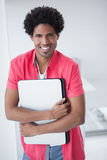Lächelnder zufälliger Geschäftsmann, der Laptop hält Stockbilder