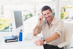Lächelnder zufälliger Geschäftsmann, der an seinem Schreibtisch arbeitet Lizenzfreie Stockfotos