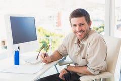 Lächelnder zufälliger Geschäftsmann an seinem Schreibtisch Lizenzfreies Stockfoto