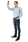 Lächelnder zufälliger Mann, der ein Foto von Ihnen macht Stockfotos