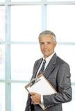 Lächelndes älteres männliches Leitprogramm mit Klemmbrett lizenzfreie stockfotos