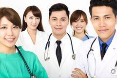 Lächelndes Ärzteteam, das zusammen auf Weiß lokalisiert steht Lizenzfreie Stockfotografie