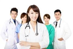 Lächelndes Ärzteteam, das zusammen auf Weiß lokalisiert steht Stockfoto