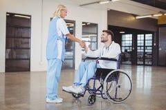 Lächelndes Ärztinhändeschütteln mit Doktor, der auf Rollstuhl sitzt Stockfoto