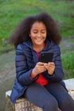Lächelndes Afrokind mit einem Mobile, das ein Foto selbst macht Stockfotos
