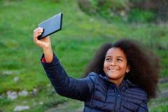 Lächelndes Afrokind mit einem Mobile, das ein Foto selbst macht Stockfotografie