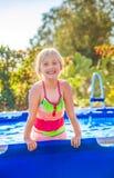 Lächelndes aktives Kind in der Badebekleidung, die im Swimmingpool spielt Stockfotografie