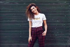 Lächelndes arabisches Mädchen in der zufälligen Kleidung in der Straße stockfotos