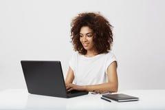 Lächelndes Arbeiten der afrikanischen Geschäftsfrau am Laptop über weißem Hintergrund Lizenzfreie Stockfotos