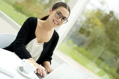 Lächelndes Arbeiten der Frau an Laptop Stockfoto