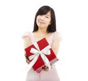 Lächelndes asiatisches Holdinggeschenk der jungen Frau Stockfoto