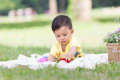 Lächelndes asiatisches Jungenkleinkind sitzen auf weißer Baumwolle in den grünen gras Stockbild