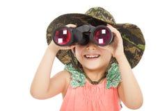 Lächelndes asiatisches kleines Mädchen, das durch Ferngläser schaut Stockfotografie