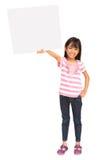 Lächelndes asiatisches kleines Mädchen, das unbelegtes Zeichen anhält Lizenzfreies Stockfoto