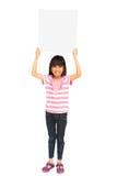 Lächelndes asiatisches kleines Mädchen, das unbelegtes Zeichen anhält Stockbild