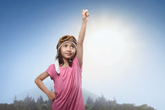 Lächelndes asiatisches kleines Mädchen im Fliegersturzhelm träumend vom Werden Lizenzfreie Stockfotos