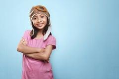 Lächelndes asiatisches kleines Mädchen mit Fliegerhut und Schutzbrillen, die fu haben Stockfotos