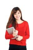 Lächelndes asiatisches Mädchen, das eine Tablette hält Stockfotos