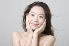 Lächelndes asiatisches Mädchen, das ihr Kinn berührt Lizenzfreies Stockbild