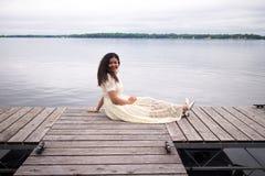 Lächelndes asiatisches Mädchen in einem weißen Kleid, das auf einem Dock sitzt stockbild