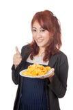 Lächelndes asiatisches Mädchen greift bis zu den Kartoffelchips ab Stockfotos