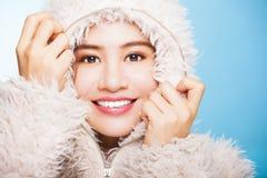 Lächelndes asiatisches Mädchen mit Winterabnutzungsstrickjacke lokalisiert auf blauem BAC Lizenzfreie Stockfotografie