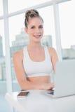 Lächelndes athletisches blondes Schreiben auf Laptop Stockfotos