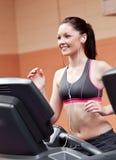 Lächelndes athletisches Frauentraining auf einer Tretmühle Stockbild