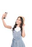 Lächelndes attraktives Brunettemädchen im Strohhut, der selfie auf Smartphone nimmt Lizenzfreie Stockfotos