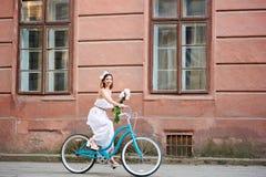 Lächelndes attraktives Mädchen im weißen Kleid, das Blumen und eine schöne alte Straße des Fahrrades unten reiten hält lizenzfreie stockfotografie
