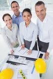 Lächelndes aufwerfendes Architektenteam beim zusammenarbeiten Stockbild