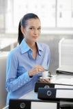 Lächelndes Büromädchen, das Kaffee trinkt Stockfotos