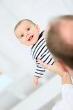 Lächelndes Baby beim Spielen mit seinem Vater Stockbild