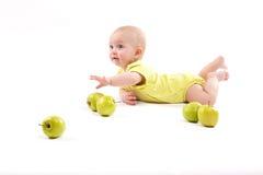 Lächelndes Baby, das auf dem Hintergrund liegt, um Äpfel mit einzuschließen Stockbild