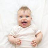 Lächelndes Baby, das auf einem weißen Bett liegt lizenzfreie stockbilder