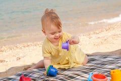 Lächelndes Baby, das auf Strand spielt stockbild