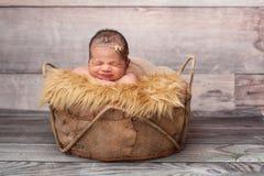 Lächelndes Baby, das in einem Korb schläft Stockfoto
