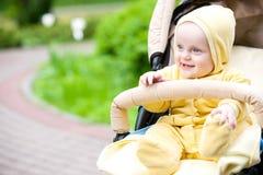 Lächelndes Baby, das in einem Spaziergänger sitzt Stockfoto