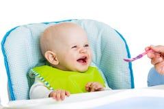 Lächelndes Baby, das Lebensmittel isst stockfoto