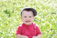 Lächelndes Baby draußen gegen Blumen Stockbilder