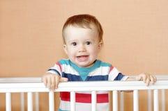 Lächelndes Baby im weißen Bett Stockfotografie