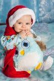 Lächelndes Baby, im Weihnachtshut und -c$halten eines Spielzeugs, beißt sie Lizenzfreies Stockbild