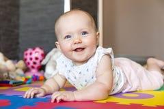 Lächelndes Baby mit den blauen Augen, die auf Boden spielen Lizenzfreie Stockfotos