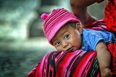 Lächelndes Baby mit großen Augen Kamera niederlegend und betrachtend Lizenzfreies Stockbild