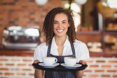 Lächelndes barista, das einen Behälter von Kaffeetassen hält Stockbild